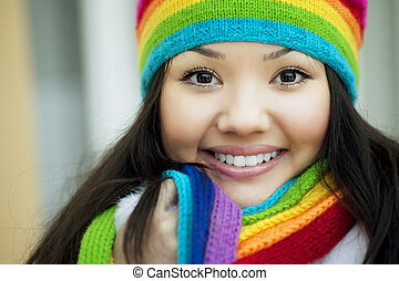 Girl in a scarf and hat of rainbow colors