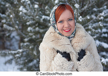 Girl in a scarf on the background of the winter forest