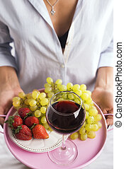 girl in a shirt holds a tray of fruit and wine