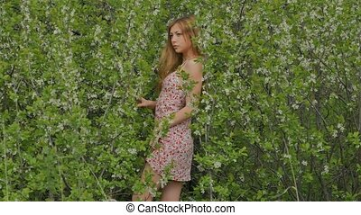 girl in a short dress in the middle of flowering blackthorn