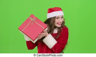 Girl in a snow maiden costume holds a gift in her hand. Green screen. Close up. Slow motion