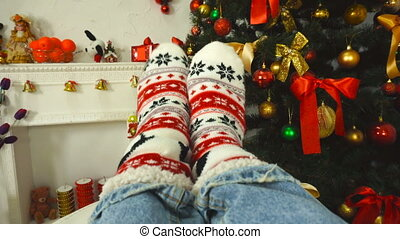 girl in a sock with ornament near the Christmas tree