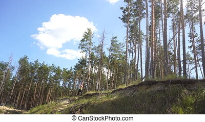 girl in a sports uniform trains in the forest summer time