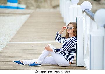Girl in a striped shirt on a white wooden background.