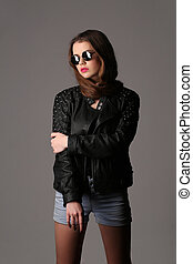 Girl in a studded leather jacket and with makeup. Close up. White background