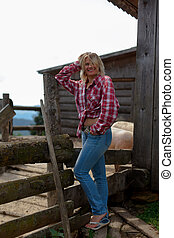 girl in a stylish men's shirt on an old farm