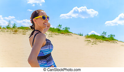 Girl in a summer dress on a beach.