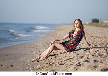 girl in a summer dress sitting on the beach