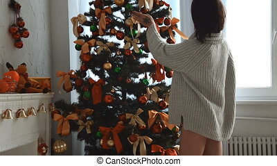girl in a sweater stands near a Christmas tree and looking at toys