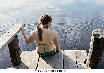 girl in a swimsuit sitting on the edge of jetty
