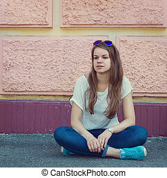 Girl in a T-shirt and jeans sitting on pavement