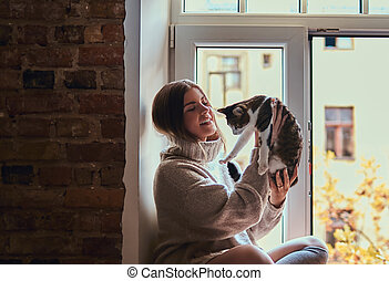 Girl in a warm sweater playing with her cat sitting on the window sill next to the open window