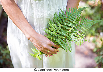 girl in a white dress, holding a green fern leaves in the forest
