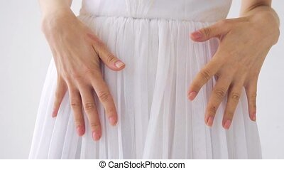 girl in a white dress holding hands on the dress