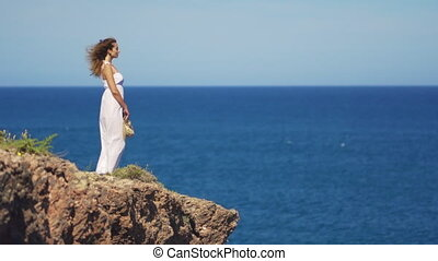 Girl in a white dress is standing on a rock cliff. a woman...