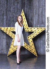 girl in a white dress on background of the star installation