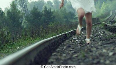 Girl in a white dress running on rails