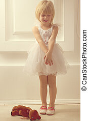 girl in a white dress with toy