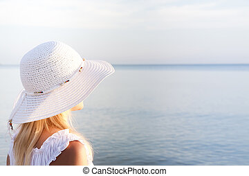 Girl in a white hat on the beach