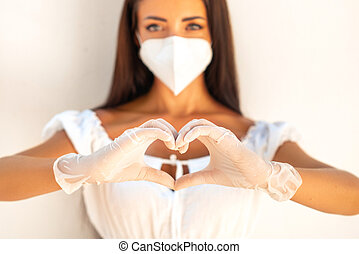 Girl in a white mask N- 95 on the background of a white wall. Girl shows gesture - heart. As a sign of love all over the world