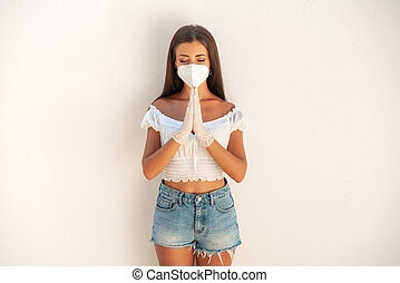 Girl in a white mask N- 95 on the background of a white wall. The girl shows a gesture - folded hands. As a sign of respect and love all over the world