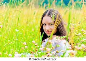 girl in a white sundress lying on green grass