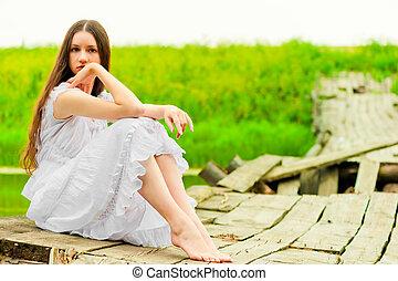 girl in a white sundress resting on the bridge