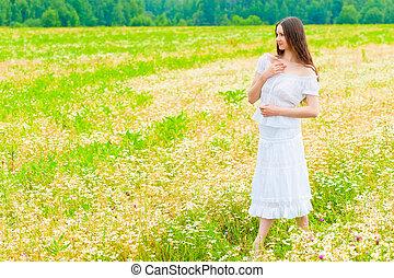 girl in a white sundress walking on chamomile field