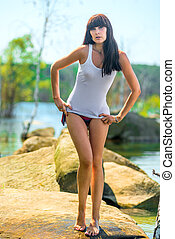 girl in a white T-shirt and bikini on the rocky shore of the lak
