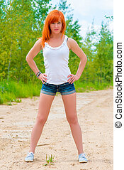girl in a white T-shirt and denim shorts posing outdoors