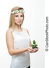 girl in a wreath of flowers holding young plant