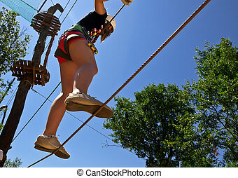 young girl climbing with care in adventure park