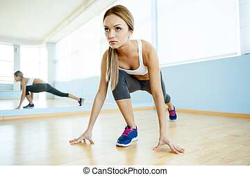 Girl in aerobics class. Beautiful young women in sports clothing exercising and smiling