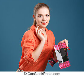 girl in an orange shirt and jeans with shopping bag on a blue ba