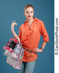 girl in an orange shirt and jeans with shopping bags on a blue b