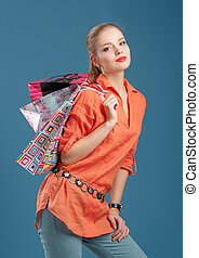 girl in an orange shirt and jeans with shopping bags