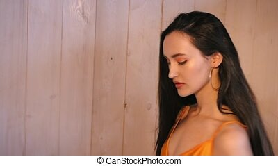 a girl in an orange dress posing in the Studio against the wall. hard light and slow motion