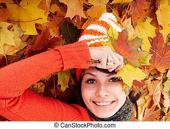 Girl in autumn orange hat on leaf group. Outdoor.