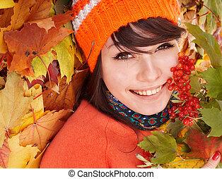 Girl in autumn orange leaves.