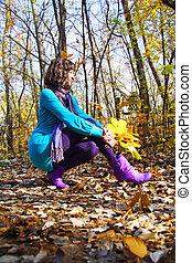 Girl in autumn orange leaves