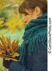 girl in autumn park with a bouquet of fallen leaves
