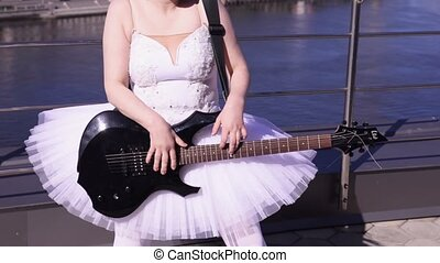 Girl in ballerina white suit play electric guitar on seafront in sunny day. Crazy dance. Rock