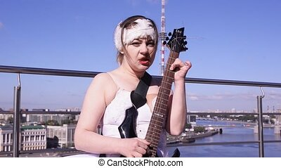 Girl in ballerina white suit play electric guitar on seafront in sunny day. Dance. Rock and roll