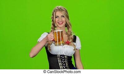 Girl in bavarian costume blows on beer foam. Slow motion. Green screen