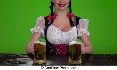 Girl in Bavarian costume breaks glasses with beer. Green...