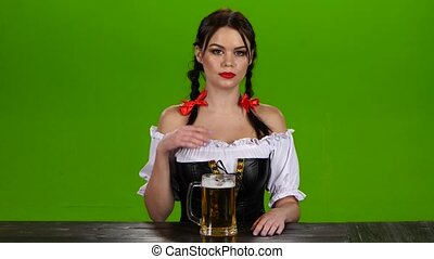 Girl in Bavarian costume celebrates Oktoberfest beer...