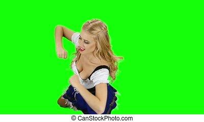 Girl in bavarian costume dancing isolated. Oktoberfest. Slow motion. Green screen