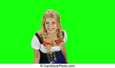 Girl in bavarian costume drinking beer from the glass and licked. Green screen