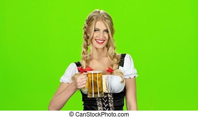 Girl in bavarian costume give someone a beer and laughs. Green screen