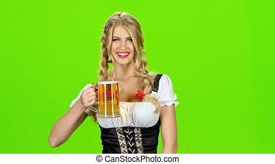 Girl in bavarian costume is enjoying a sip of beer. Green...